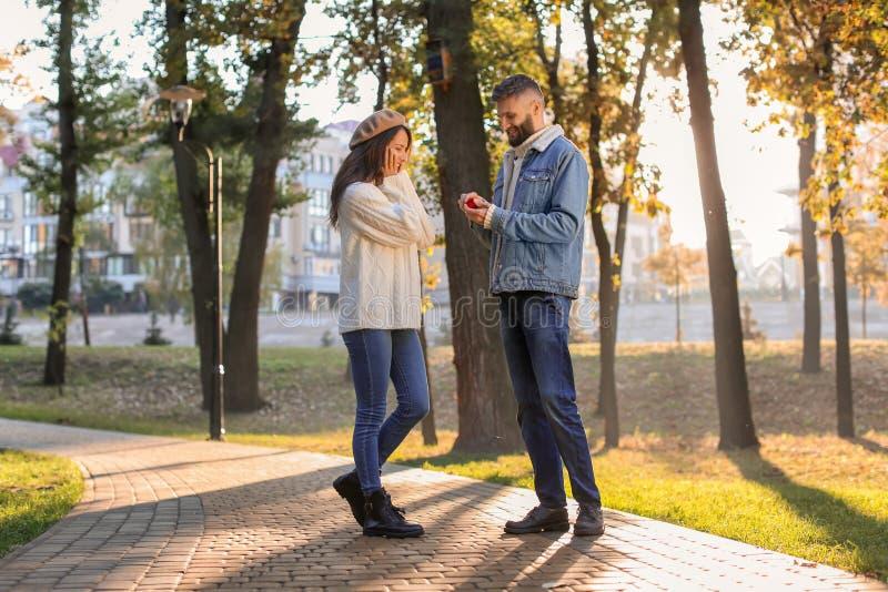 Homem novo que propõe ao seu amado no parque do outono fotografia de stock royalty free