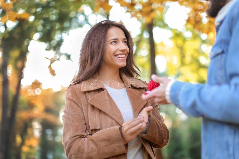 Homem novo que propõe ao seu amado no parque do outono imagem de stock