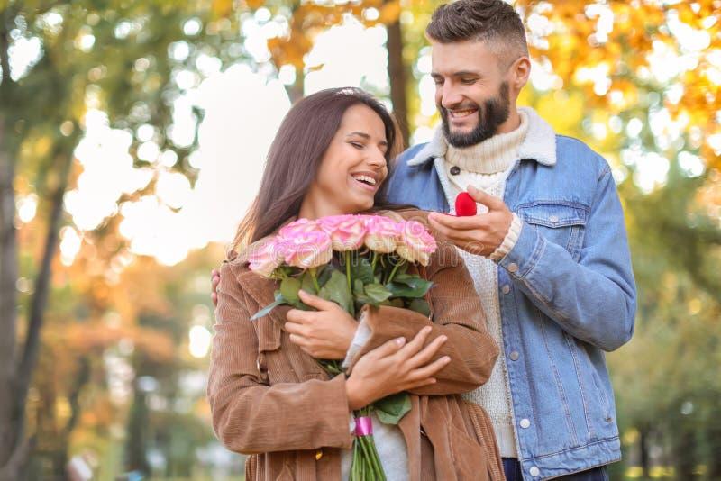 Homem novo que propõe ao seu amado no parque do outono imagens de stock royalty free