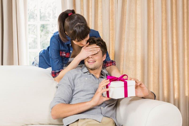 Homem novo que recebe um presente da surpresa foto de stock