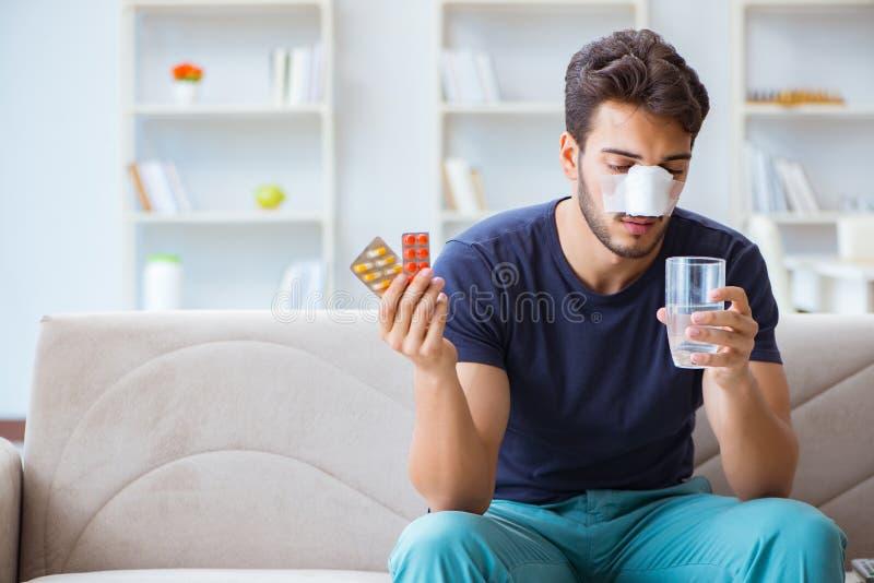 Homem novo que recupera a cura em casa após o nariz da cirurgia plástica fotos de stock