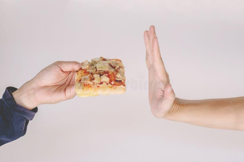 Homem novo que rejeita a pizza ou o alimento insalubre E Conceito insalubre comer imagens de stock