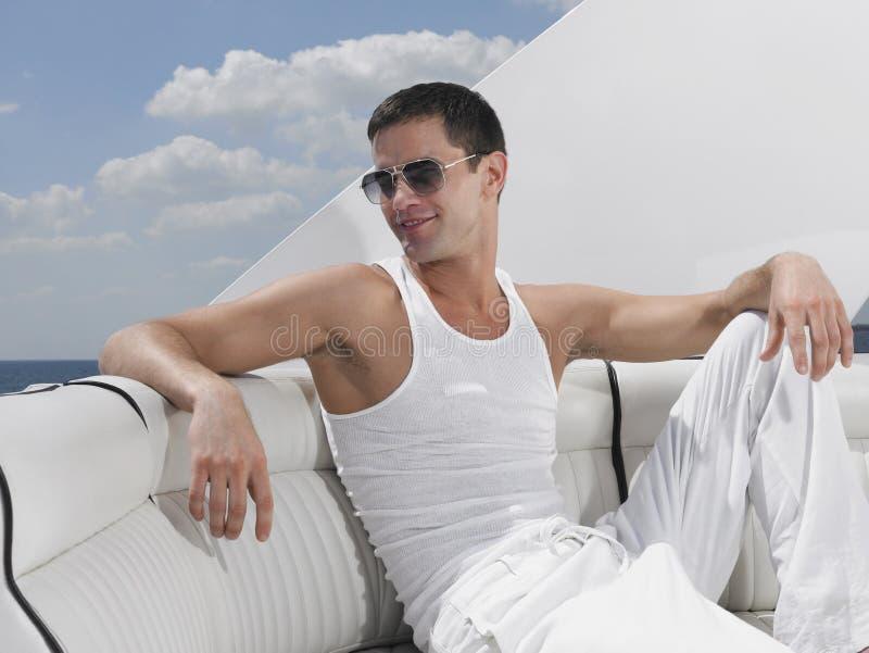 Homem novo que relaxa no iate luxuoso fotografia de stock royalty free
