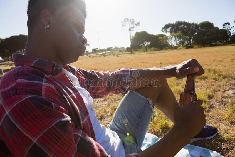 Homem novo que relaxa no parque em um dia ensolarado foto de stock royalty free