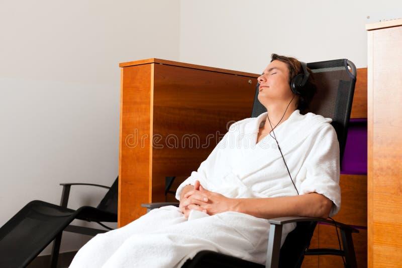 Homem novo que relaxa nos termas com música imagens de stock