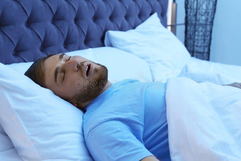Homem novo que ressona ao dormir na cama na noite fotos de stock