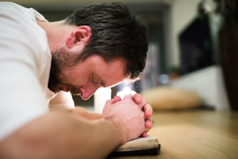 Homem novo que reza, ajoelhando-se no assoalho, mãos na Bíblia imagem de stock royalty free