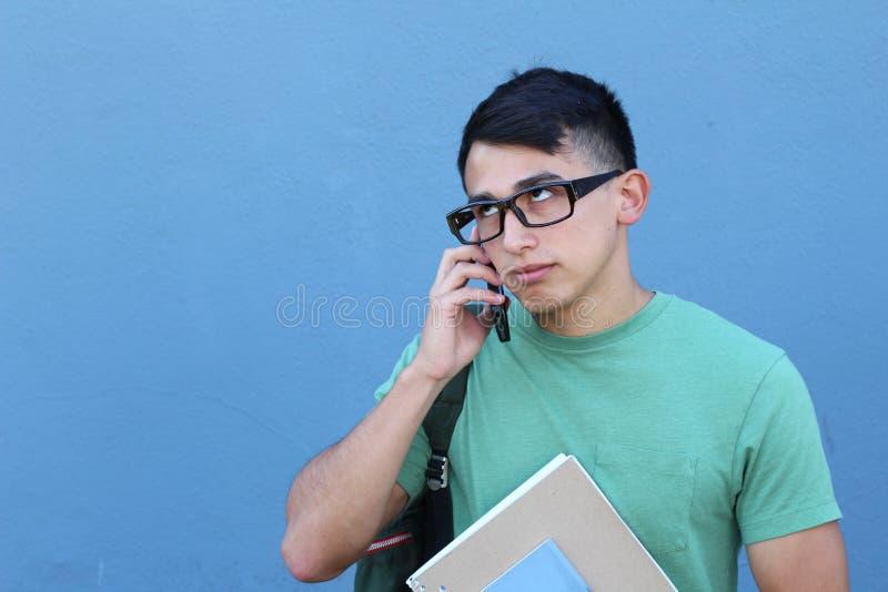 Homem novo que rola seus olhos em consequência chamar seu telefone celular com espaço para a cópia fotografia de stock royalty free