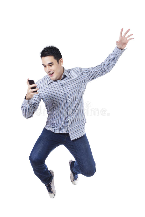 Homem novo que salta com um telemóvel imagem de stock