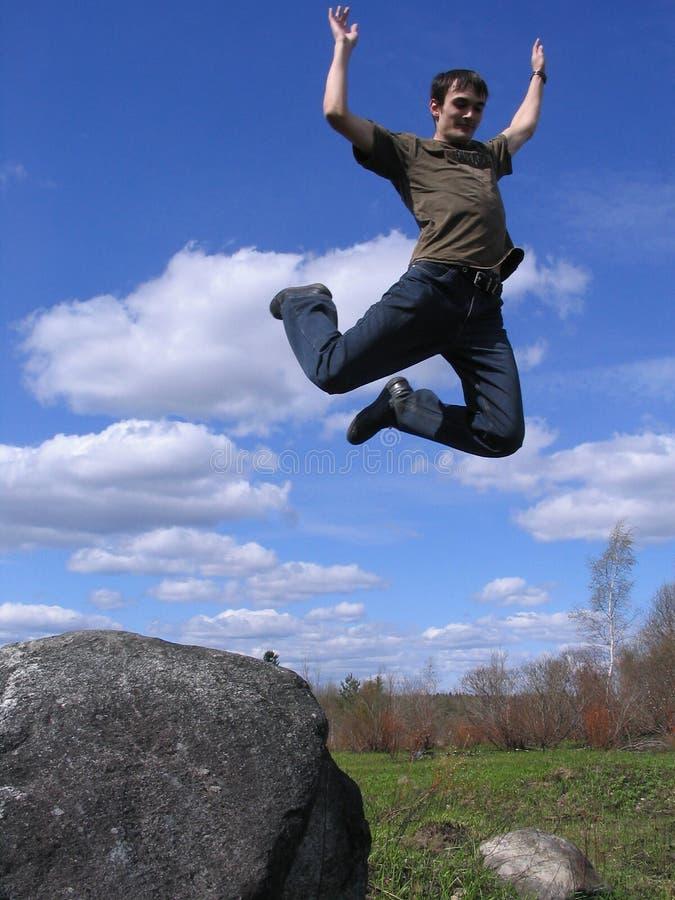 Homem novo que salta da pedra 2 fotografia de stock