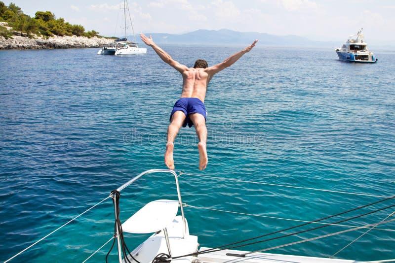 Homem novo que salta de um barco de navigação. imagem de stock royalty free