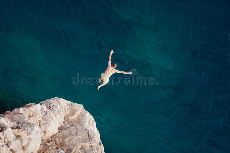 Homem novo que salta do penhasco no mar imagem de stock royalty free