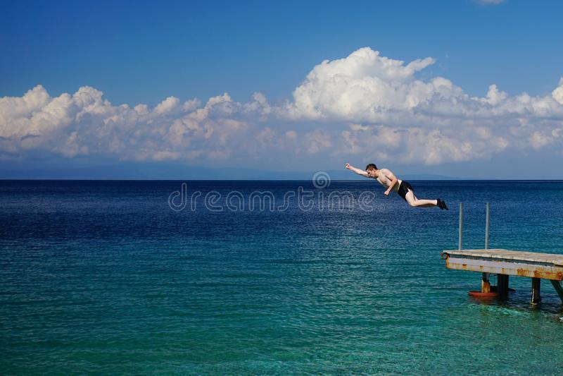 Homem novo que salta fora do cais na água foto de stock