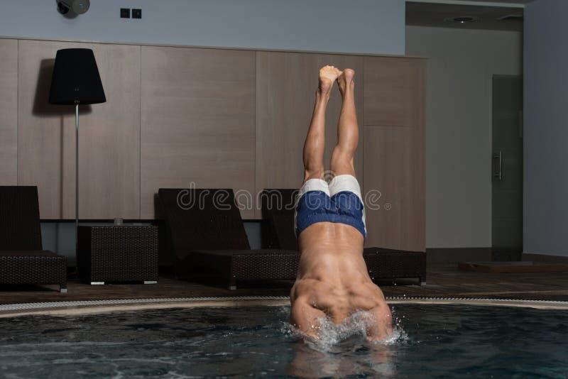Homem novo que salta na água imagens de stock