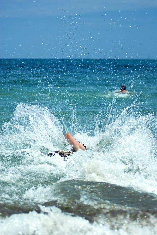 Homem novo que salta na água de mar foto de stock royalty free