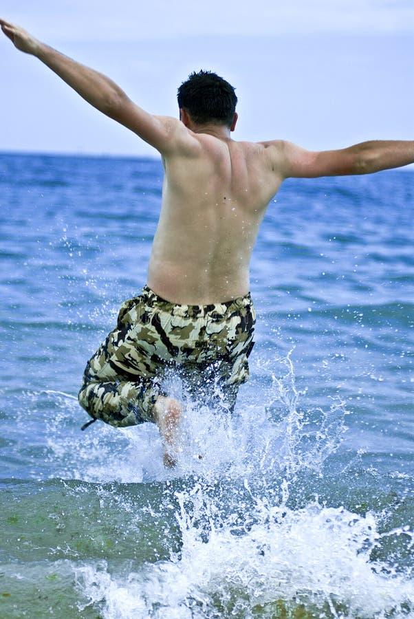 Homem novo que salta na água de mar fotografia de stock royalty free