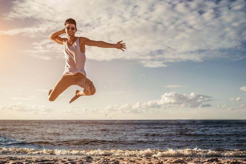 Homem novo que salta na praia imagens de stock royalty free