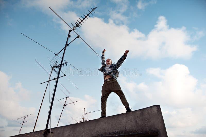 Homem novo que salta no telhado com o céu azul brilhante e as nuvens brancas no fundo imagens de stock royalty free