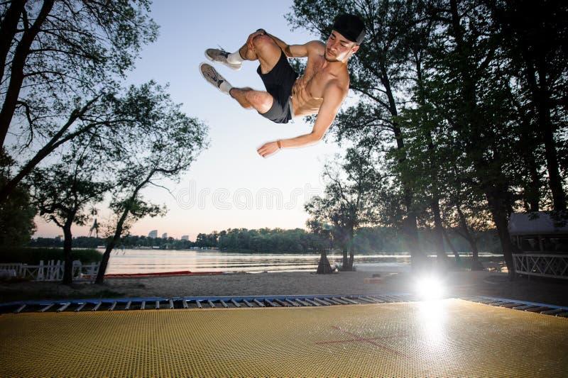 Homem novo que salta no trampolim amarelo fotos de stock