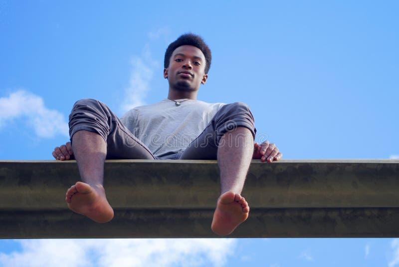 Homem novo que senta o céu azul descalço de opinião de baixo ângulo foto de stock royalty free