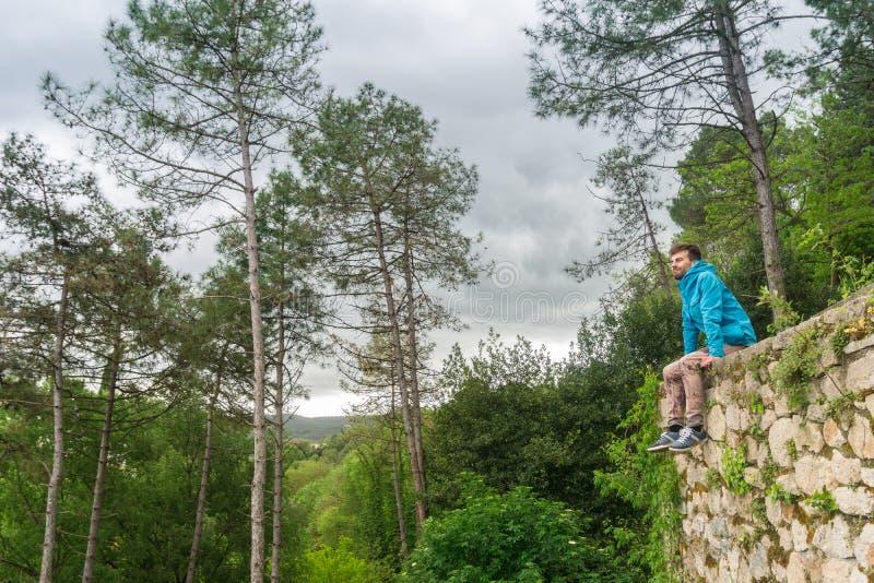 Homem novo que senta-se apenas na parede de pedra exterior com a floresta no fundo Homem no conceito da natureza imagem de stock royalty free