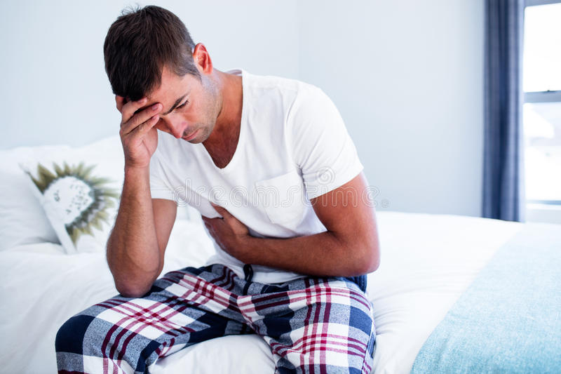 Homem novo que senta-se com dor de estômago na cama foto de stock royalty free