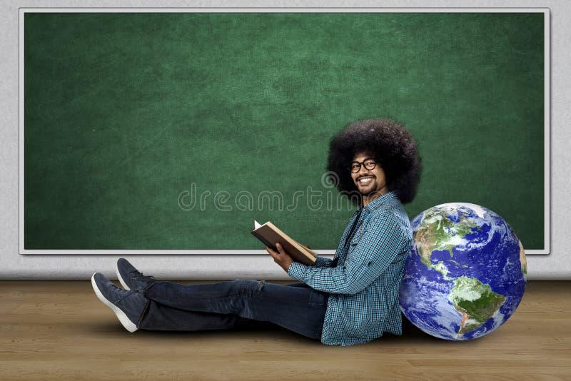 Homem novo que senta-se com globo e livro imagens de stock