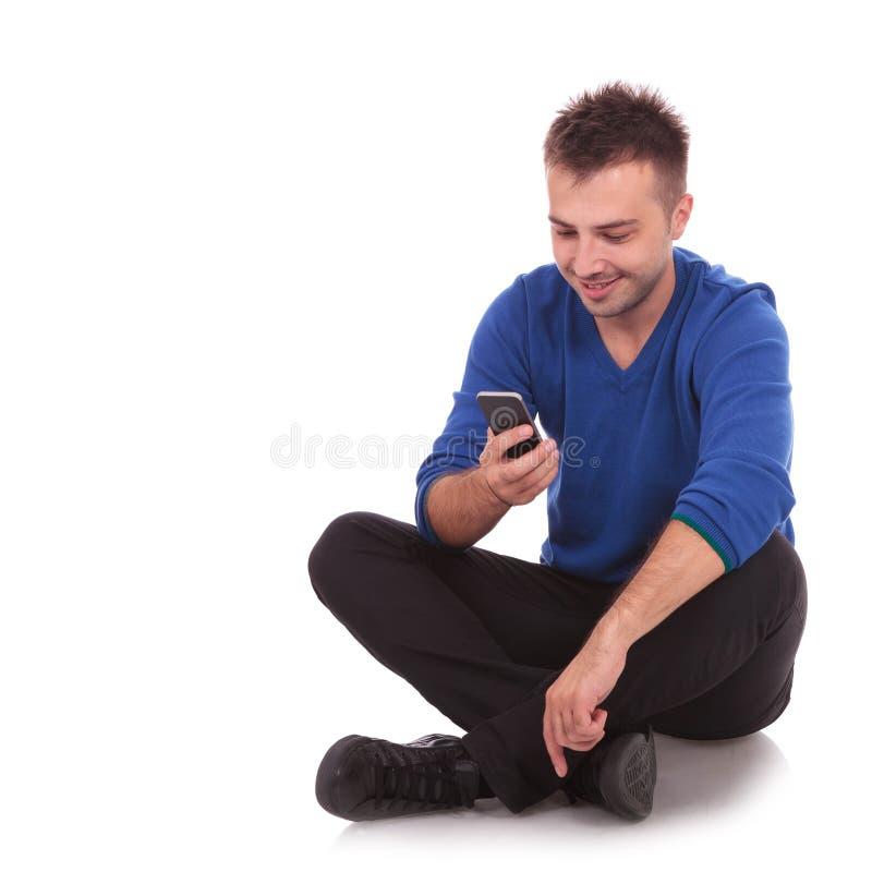 Homem novo que senta-se e que texting em seu smartphone fotografia de stock royalty free