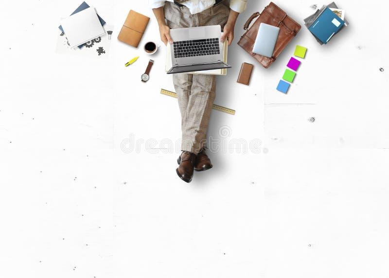 Homem novo que senta-se e que trabalha no assoalho com livro e portátil imagem de stock