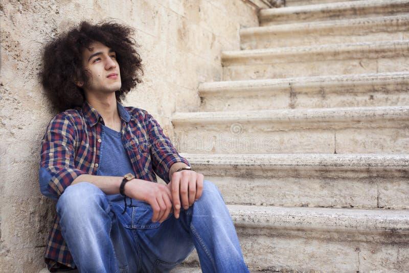 Homem novo que senta-se em escadas fotos de stock