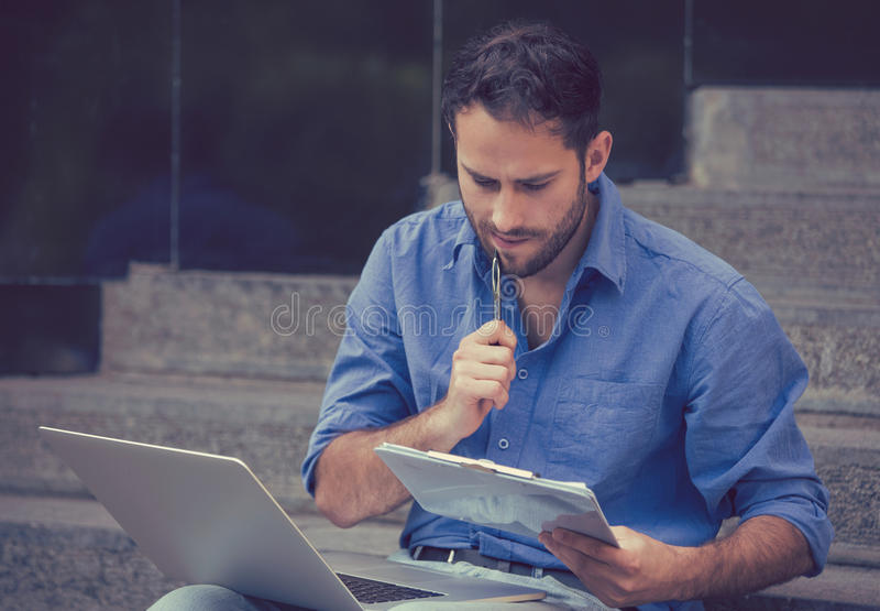 Homem novo que senta-se em etapas fora da construção incorporada da cidade usando um portátil fotos de stock