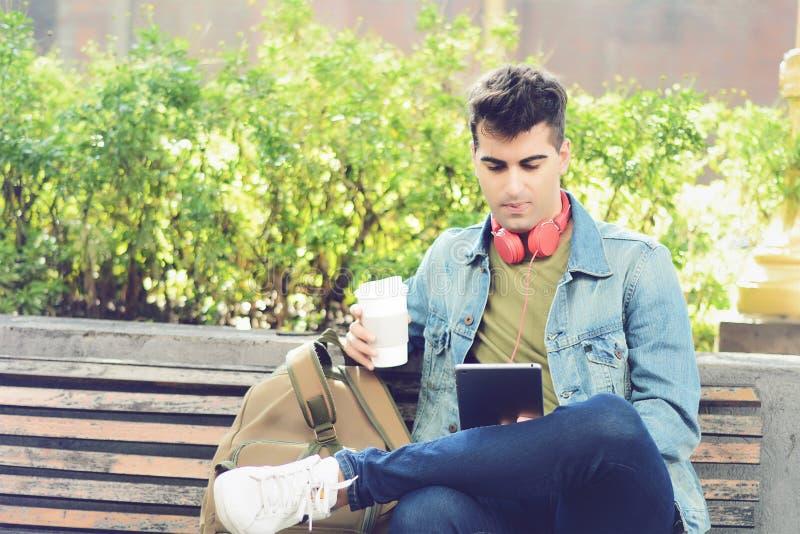 Homem novo que senta-se em um banco com tabuleta e café bebendo imagem de stock royalty free