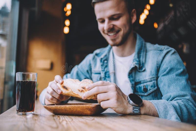 Homem novo que senta-se em um restaurante e que come um Hamburger imagem de stock
