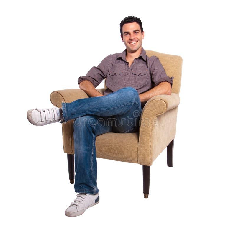 Homem novo que senta-se em um sofá imagens de stock