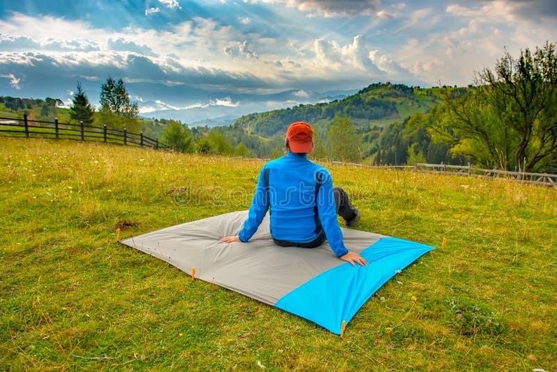 Homem novo que senta-se em uma cobertura de nylon impermeável em uma paisagem bonita da montanha e que aprecia a vista Conceito d fotografia de stock royalty free