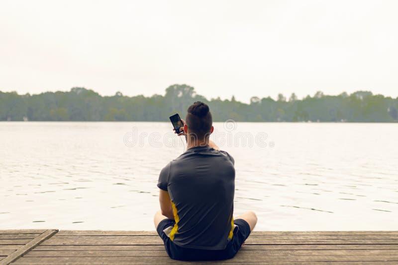 Homem novo que senta-se em uma plataforma de madeira acima de um lago foto de stock
