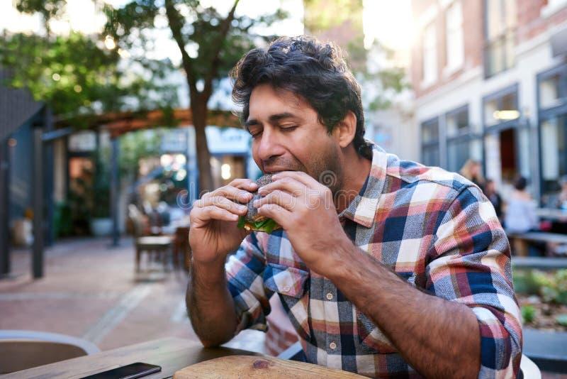 Homem novo que senta-se fora de comer um bagel delicioso da semente de papoila fotografia de stock royalty free