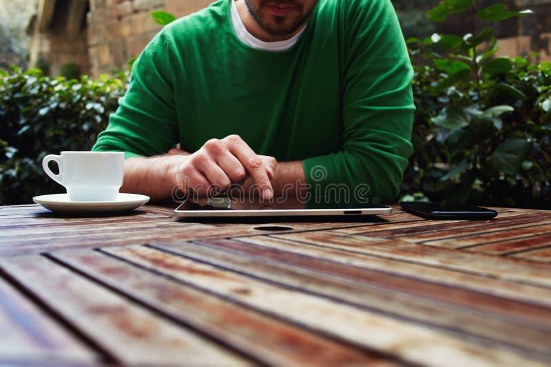 Homem novo que senta-se na tabela com xícara de café foto de stock