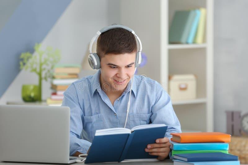 Homem novo que senta-se na tabela e que escuta o livro fotos de stock