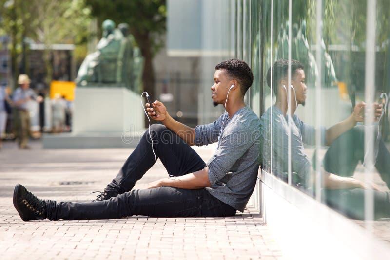 Homem novo que senta-se na terra que escuta a música no telefone esperto fotografia de stock
