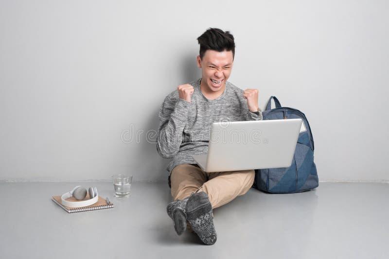 Homem novo que senta-se no assoalho e que usa o portátil imagens de stock