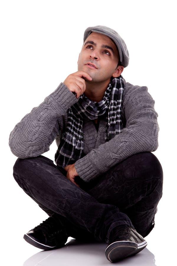 Homem novo que senta-se no assoalho, pensando imagens de stock