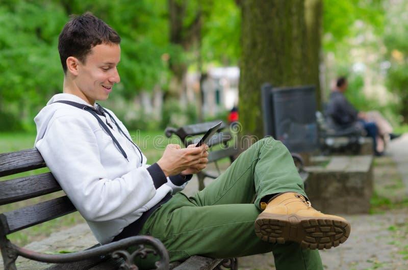 Homem novo que senta-se no banco e que usa o dispositivo da tabuleta no beauti fotografia de stock