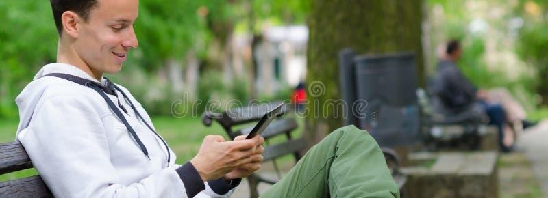 Homem novo que senta-se no banco e que usa o dispositivo da tabuleta no beauti imagens de stock