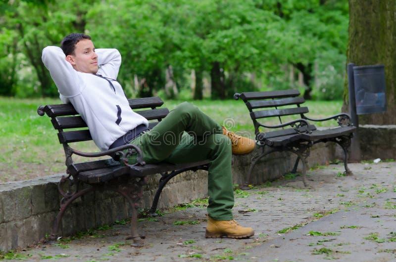 Homem novo que senta-se no banco no parque fotografia de stock royalty free