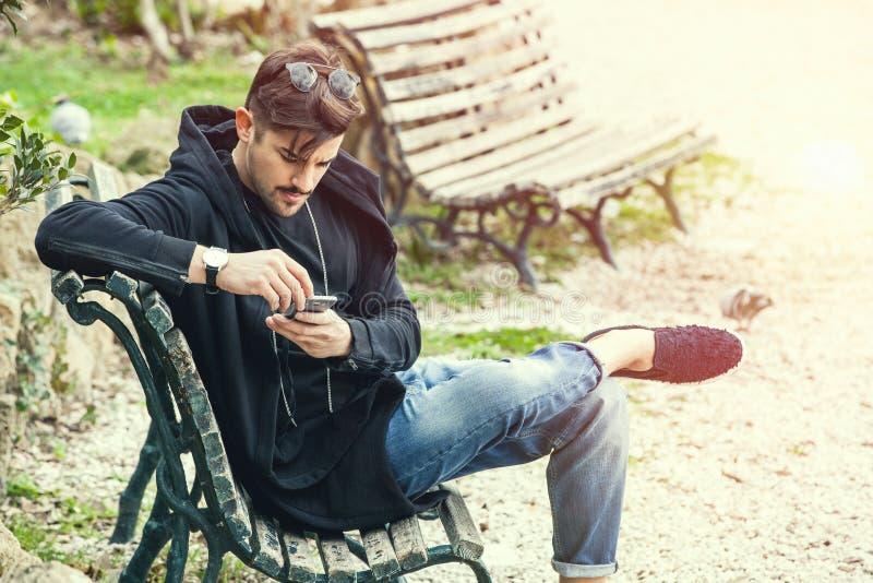 Homem novo que senta-se no banco que espera com telefone à disposição fotografia de stock