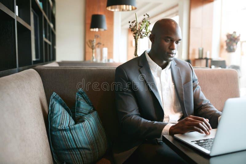 Homem novo que senta-se no café que trabalha no portátil imagem de stock