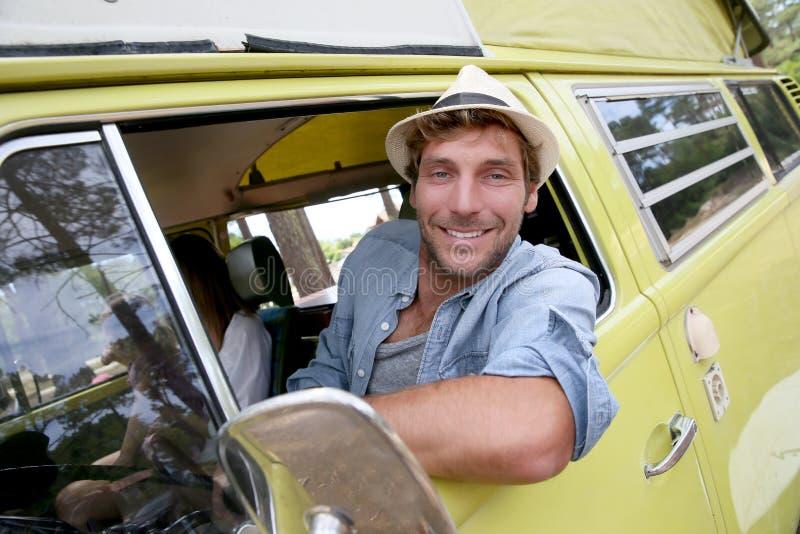 Homem novo que senta-se no carro de acampamento do vintage imagem de stock