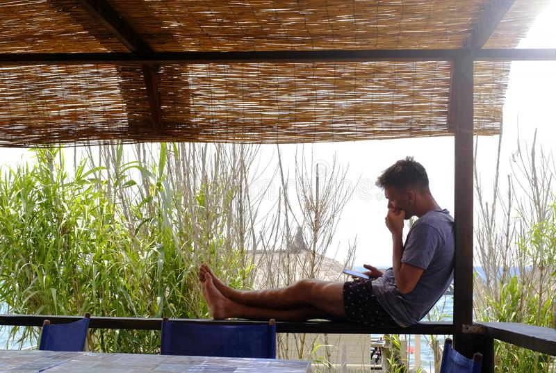 Homem novo que senta-se no miradouro ao olhar seu smartphone No fundo as palhas criam uma cena tropical foto de stock