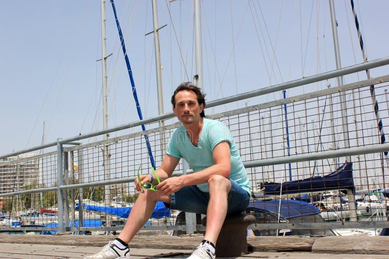 Homem novo que senta-se no poste de amarração no cais com barreira no porto imagens de stock royalty free